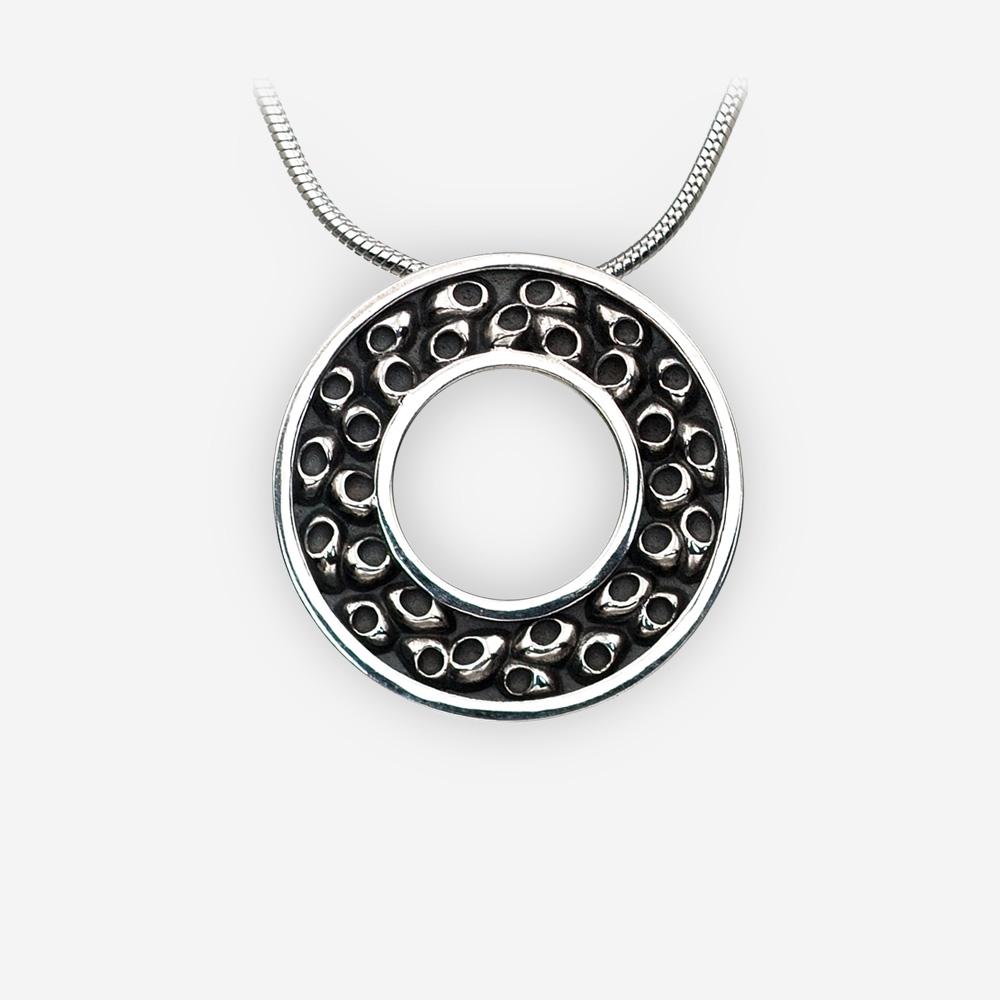 Pendiente redondo de plata ennegrecido con un patrón en relieve.