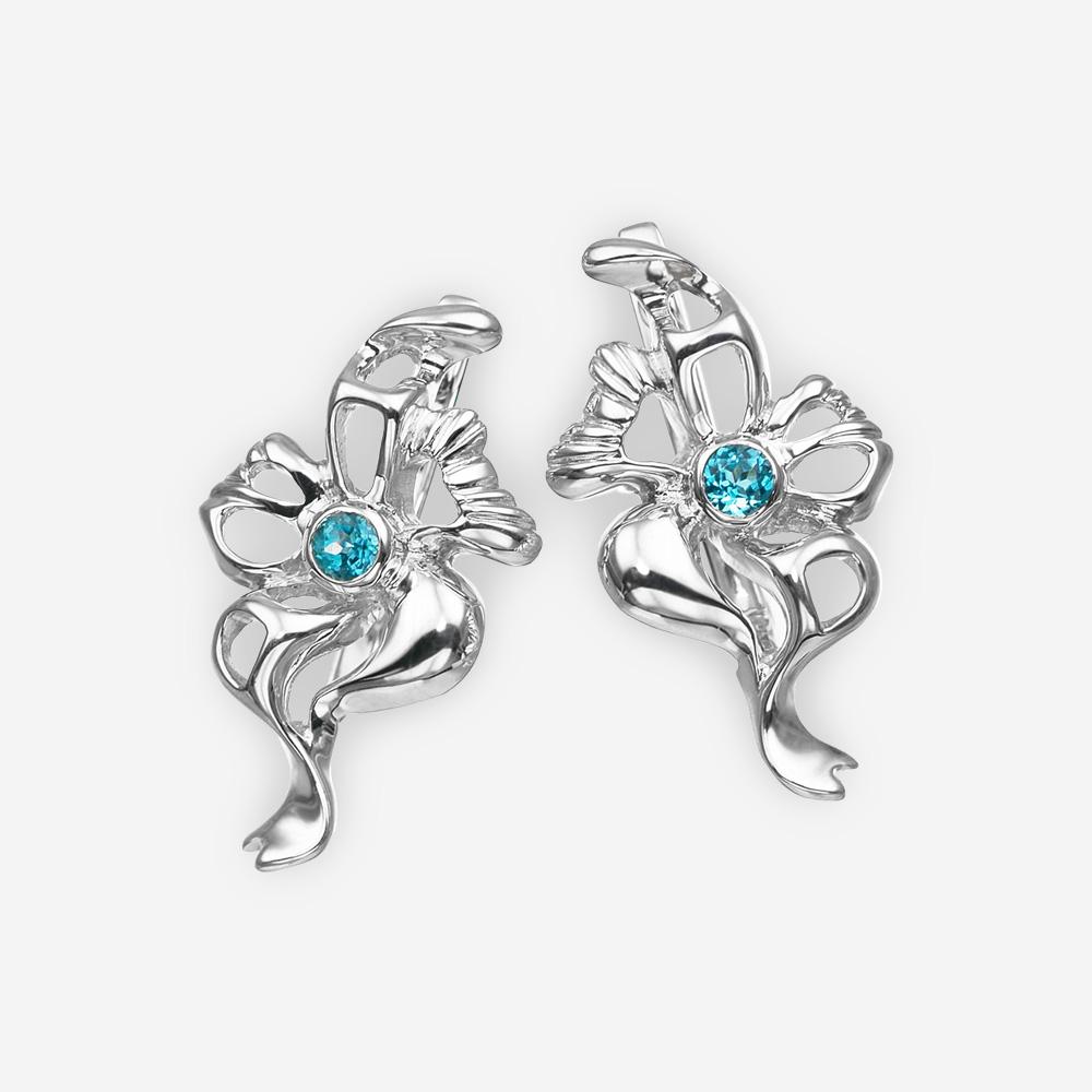 Aretes de plata en forma de flor con topacio azul y detalles a cielo abierto.