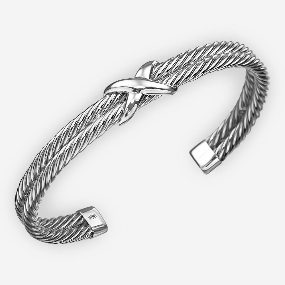 Brazalete de cable trenzado de plata fina. Se compone de dos brazaletes con patrón de cable retorcido y un punto focal cruzado.