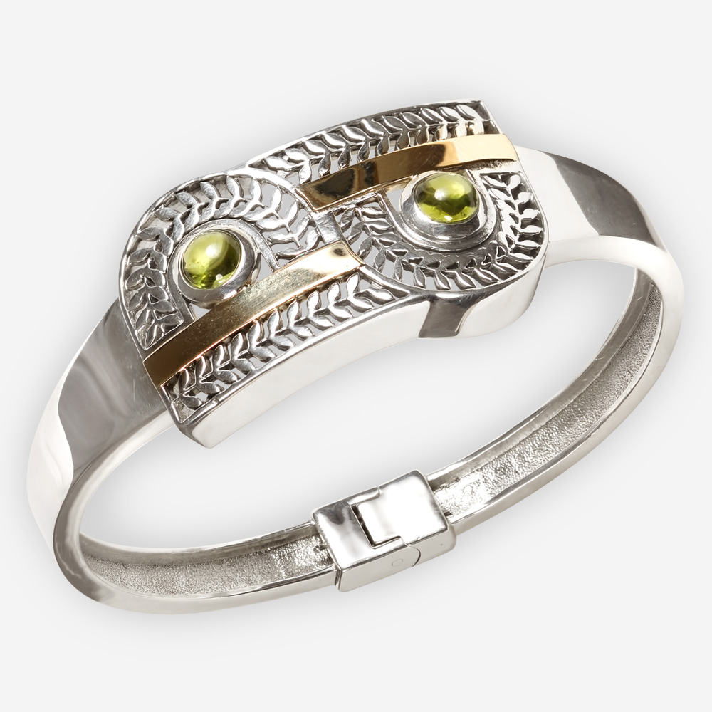 Exotic silver cutout bangle is crafted from 925 sterling silver, 14k gold and feature a cutout leaf design and two gemstone cabochons.