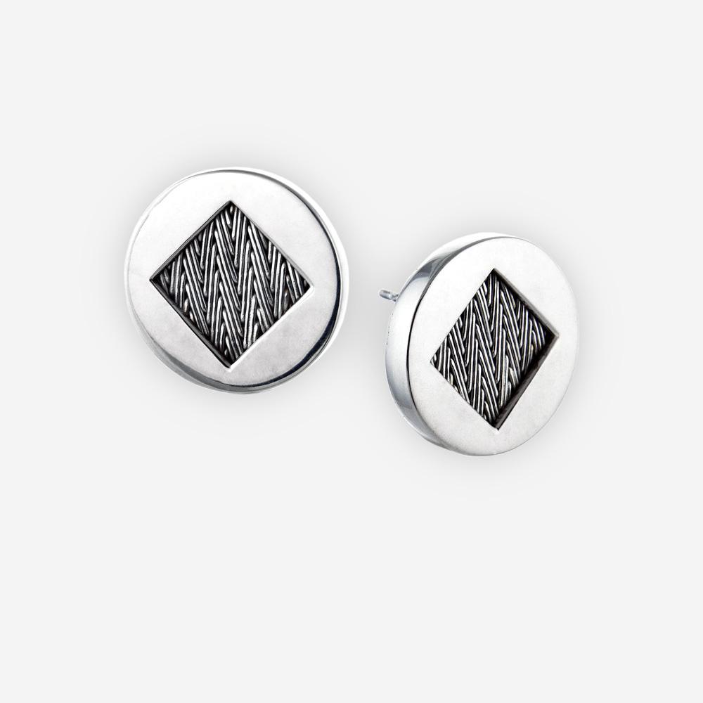 Aretes circulares de plata fina con diseño de tejido a mano en el centro.
