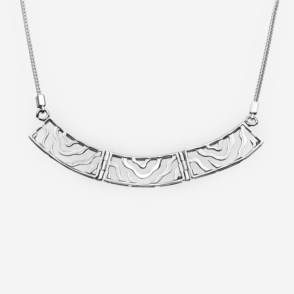 Collar de plata moderno con enlaces de diseño de onda abstracta recortada que cuelgan de una cadena retorcida.