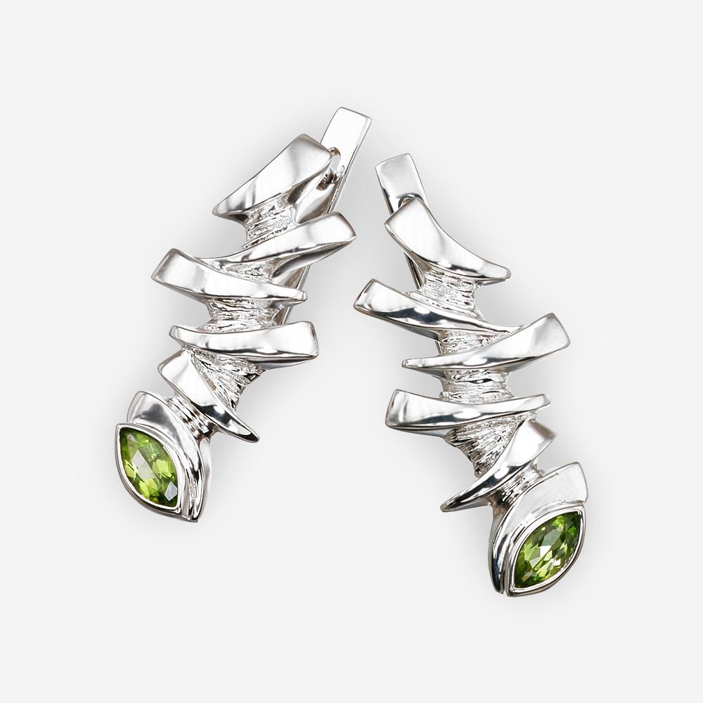 Aretes de plata en forma de ojo de dragón con gemas de peridoto.